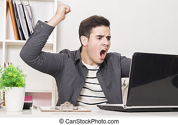 young man celebrating enthusiastically in front of laptop...