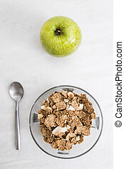 bowl of cereal integral with the spoon and apple on...