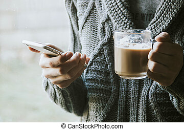 hands with the mobile phone and the cup of coffee next to...