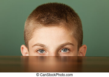 Boy peeping out table surface - Close-up of young boy with...