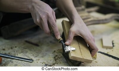 Attractive carpenter is restoring the wood element of some furniture.