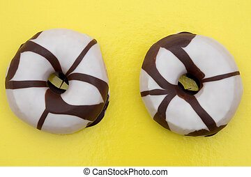 couple of donuts from chocolate and white on yellow...