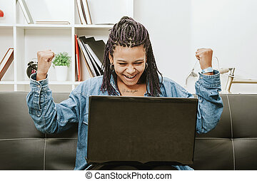 female young african descent with the computer in house...