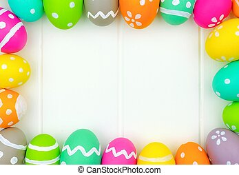 Colorful Easter egg frame around a white wood background