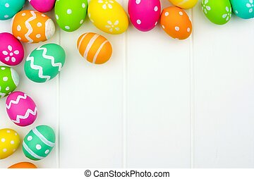 Colorful Easter egg corner border against a white wood...