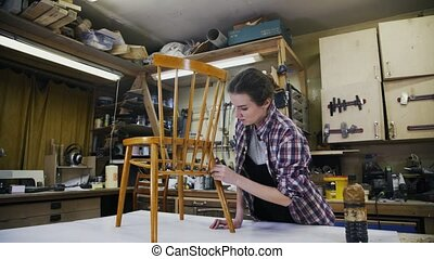 A carpenter is restoring the wooden chair. Master shot....
