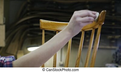 A carpenter is restoring the wooden chair. Closeup. - A...