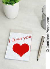 message of love in the book on the desk, valentine´s day top view