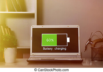 computer laptop charging the battery pack in the room at...