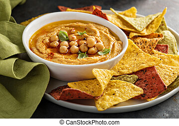 Homemade hummus in white bowl with rainbow corn chips -...