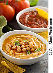 Homemade hummus and tomato salsa in white bowls with chips -...