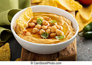 Homemade hummus in white bowl with corn chips - Homemade...