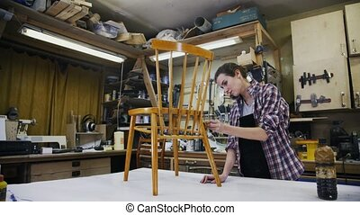 A carpenter is restoring the wooden chair. Master locked down shot. Workshop.