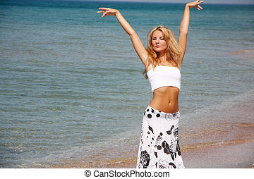 young beautiful woman posing on sea background