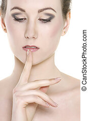 close up of beautiful woman with finger at her lips