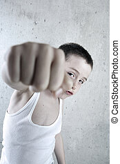 Aggression - A young boy with his fist punching at the...