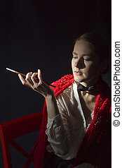 Charming lady with mouthpiece in a red shawl on a black...