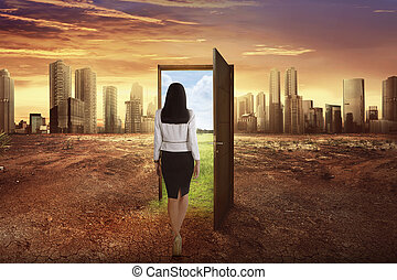 Asian business woman walking to the open wooden door with green environment