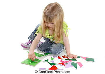 cute girl playing with colorful puzzle over white