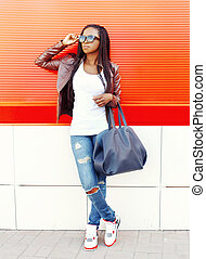 Fashion african woman with bag in city over red background