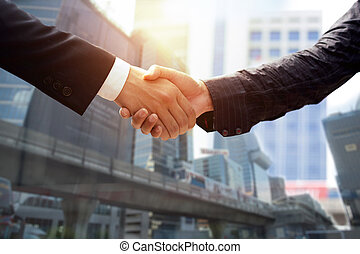 Business agreement success hand shaking in front of modern...