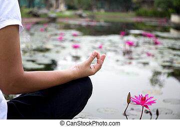 Woman doing yoga meditation next to lotus pond