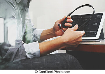 business man using VOIP headset with digital tablet computer docking smart keyboard, concept communication, it support,on wood desk