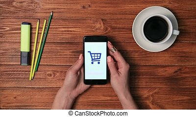 Young female making purchase in e-shop with phone - Top view...