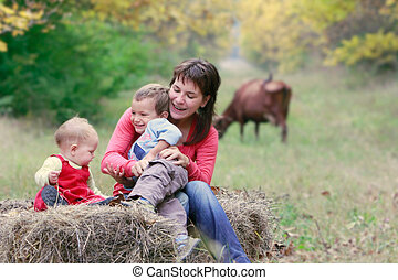 mother playing with two kids on nature