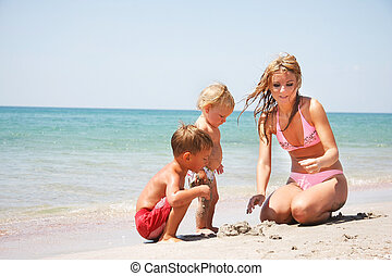 mother with two kids on beach