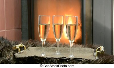By the fireplace three glasses with champagne stand on a...