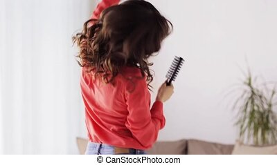 woman with hairbrush singing and dancing at home - people,...