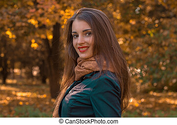 beautiful girl with red lipstick on lips stands in the Park by turning her head to the camera and smiling