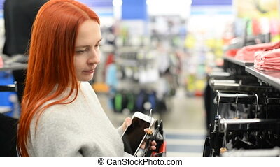 Attractive young woman shopping for clothes - Attractive red...