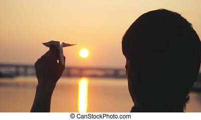 Silhouette of man launch paper plane against the sea during...