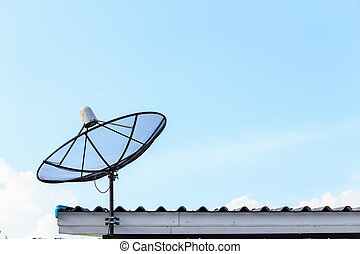 Black satellite install on the house roof with blue sky...