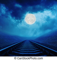 full moon in night clouds over railroad