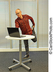 middle age male leg exercise during standing office work -...
