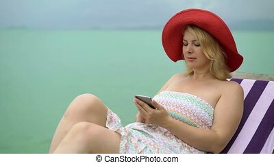Young woman on a beach chair with mobile