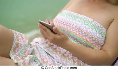 Young woman on a beach chair with mobile phone