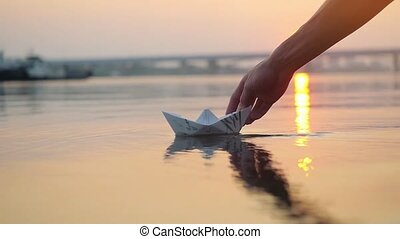 Man's hand putting paper boat on the water and pushing it away during beautiful sunset with reflection sun in the sea in slowmotion. 1920x1080