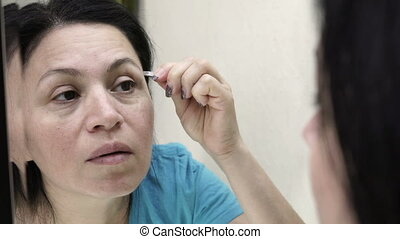 Woman Looking into Mirror Plucking Eyebrows Handheld - Over...