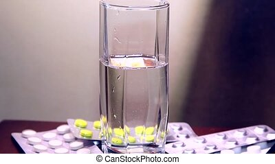 Drugs. Water poured into glass and falls aspirin tablet into...