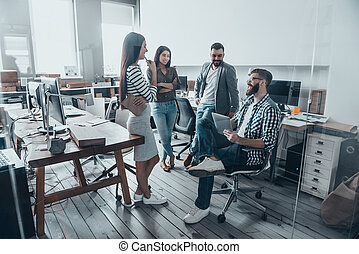 Day meeting. Handsome young man in casual wear and eyeglasses sitting on chair and holding digital tablet while his colleagues standing around him in office