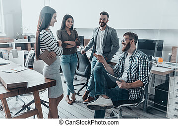 Quick meeting. Handsome young man in casual wear and eyeglasses sitting on chair and gesturing while his colleagues standing around him in office