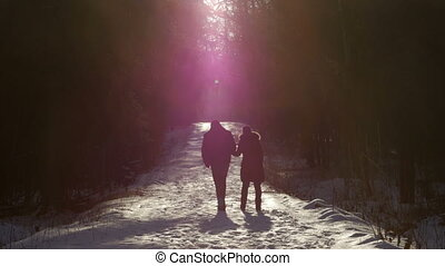 This is a shot of a young couple in love walking in picturesque winter park with snow holding hands at sunny day.