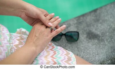 Woman with ring on finger, pool on background