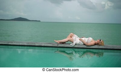 Young woman relaxing near pool