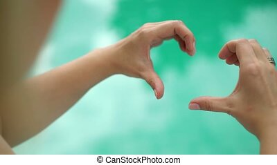 Woman shows heart by hands, pool on background
