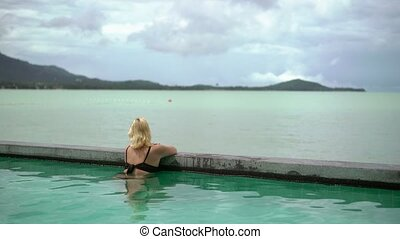 Woman relaxing in pool in resort
